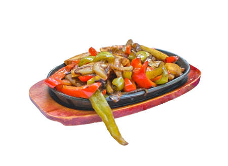 tex: Plate with fried Tex Mex vegetables such as onion and peppers on wood and black iron plates isolated on white Stock Photo