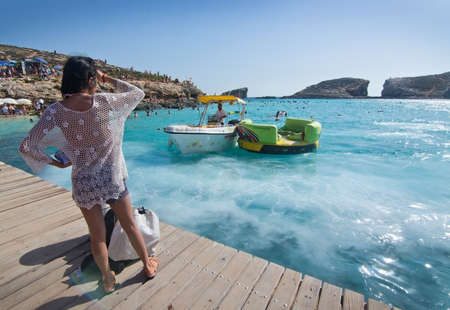 blue lagoon: BLUE LAGOON, COMINO, MALTA - SEPTEMBER 16, 2015: Young woman watches boats foaming in the clear turquoise water of popular tourist attraction Blue Lagoon on a sunny day in September 16, 2015 in Comino island, Malta.
