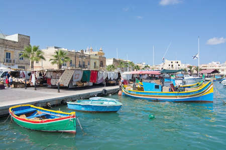 colorfully: MARSAXLOKK, MALTA - SEPTEMBER 15, 2015: Colorfully painted small wooden boats moored in the clear turquoise water of popular fishing village and market on a sunny day on September 15, 2015 in Marsaxlokk, Malta.