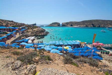 blue lagoon: Laguna blu, Comino, MALTA - 16 settembre, 2015: I visitatori affollano per godere l'acqua turchese del popolare attrazione turistica Blue Lagoon sotto gli ombrelloni in una giornata di sole in 16 SETTEMBRE 2015 nell'isola di Comino, Malta. Editoriali
