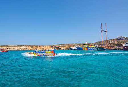 blue lagoon: BLUE LAGOON, COMINO, MALTA - SEPTEMBER 16, 2015: Tour boats moor in the clear turquoise water of popular tourist attraction Blue Lagoon on a sunny day in September 16, 2015 in Comino island, Malta.