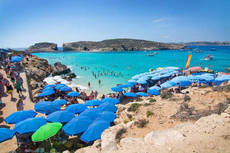 blue lagoon: BLUE LAGOON, COMINO, MALTA - SEPTEMBER 16, 2015: Visitors crowd to enjoy the clear turquoise water of popular tourist attraction Blue Lagoon under  umbrellas on a sunny day in September 16, 2015 in Comino island, Malta.