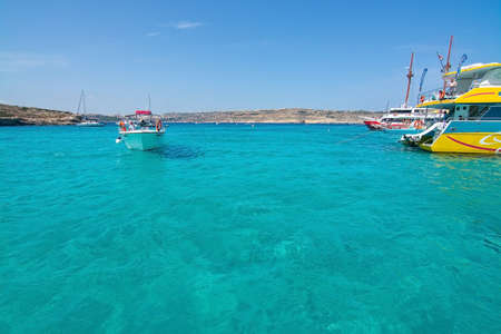 tour boats: BLUE LAGOON, COMINO, MALTA - SEPTEMBER 16, 2015: Tour boats moor in the clear turquoise water of popular tourist attraction Blue Lagoon on a sunny day in September 16, 2015 in Comino island, Malta.