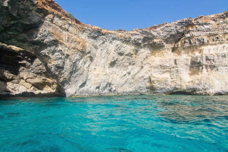limestone caves: Limestone rock with caves and blue turquoise Mediterranean ocean water near Comino island, Malta.
