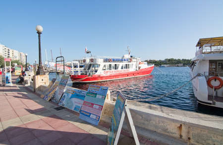 tour boats: SLIEMA, MALTA - SEPTEMBER 15, 2015: Tour boats and posters in the Sliema Ferries terminal on a sunny afternoon on September 15, 2015 in Sliema, Malta.