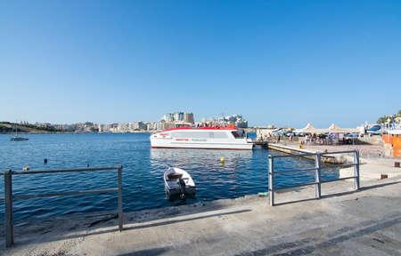 ferries: SLIEMA, MALTA - SEPTEMBER 15, 2015: Commuter boat in port at the Valletta Ferries terminal on September 15, 2015 in Valletta, Malta.
