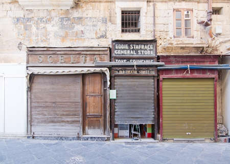 fronts: VALLETTA, MALTA - SEPTEMBER 15, 2015: City scene in the streets of Valletta with old architecture and vintage store fronts on a sunny day in September 15, 2015 in Valletta, Malta.