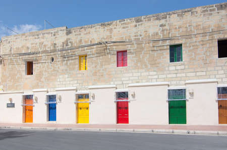 MARSAXLOKK, MALTA - SEPTEMBER 15, 2015: Colorful doors facing the ocean with plastic drapes protecting against salty or sandy winds at the Quayside Apartments on a sunny day in September 15, 2015 in Marsaxlokk, Malta. Editorial