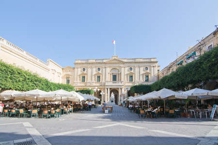 VALLETTA, MALTA - SEPTEMBER 15, 2015: Caffe Cordina outdoor restaurant and cafe and the National Library classical baroque building on a sunny day in September 15, 2015 in Valletta, Malta.