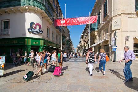 wembley: VALLETTA, MALTA - SEPTEMBER 15, 2015: Pedestrians walk in streets of Valletta outside Wembley store on a sunny day in September 15, 2015 in Valletta, Malta. Editorial