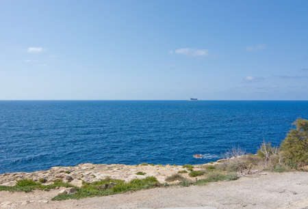 clear away: BLUE GROTTO, MALTA - SEPTEMBER 15, 2015: Boat with people in the clear turquoise water of popular tourist attraction Blue Grotto and dramatic bird island Filfla far away on a sunny day in September 15, 2015 in Malta.