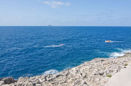 tour boats: BLUE GROTTO, MALTA - SEPTEMBER 15, 2015: Tour boats at sea and bird protection area island in the popular tourist attraction Blue Grotto on a sunny day in September 15, 2015 in Malta.