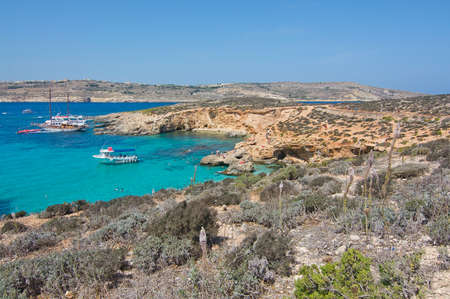 blue lagoon: BLUE LAGOON, COMINO, MALTA - SEPTEMBER 16, 2015: Tour boats in the clear turquoise water and arid landscape of popular tourist attraction Blue Lagoon on a sunny day in September 16, 2015 in Comino island, Malta. Editoriali