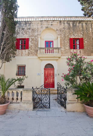 red shutters: MDINA, MALTA - SEPTEMBER 15, 2015: Beautiful residential building inside Mdina wall with red doors, balcony, window shutters and entrance in black wrought iron on a sunny day in September 14, 2015 in Mdina, Malta.