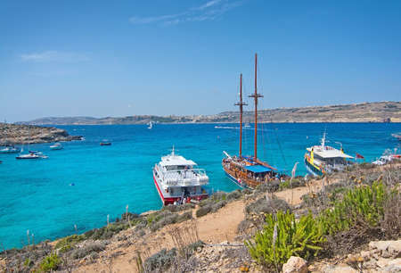 tour boats: BLUE LAGOON, COMINO, MALTA - SEPTEMBER 16, 2015: Tour boats in the clear turquoise water and arid landscape of popular tourist attraction Blue Lagoon on a sunny day in September 16, 2015 in Comino island, Malta. Editorial