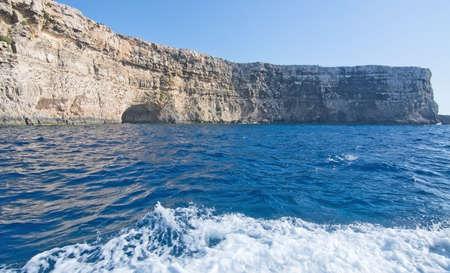 limestone caves: Limestone rock with caves and blue Mediterranean ocean water near Comino island, Malta.