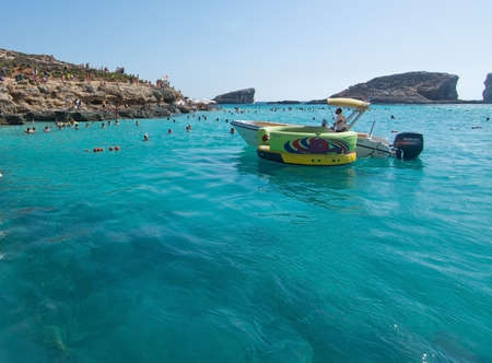 blue lagoon: BLUE LAGOON, COMINO, MALTA - SEPTEMBER 16, 2015: Boats in the clear turquoise water of popular tourist attraction Blue Lagoon on a sunny day in September 16, 2015 in Comino island, Malta.