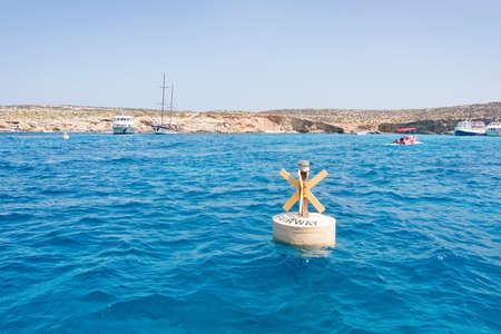 tour boats: BLUE LAGOON, COMINO, MALTA - SEPTEMBER 16, 2015: Yellow small light buoy tour boats moor in the clear turquoise water of popular tourist attraction Blue Lagoon on a sunny day in September 16, 2015 in Comino island, Malta.