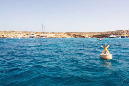 blue lagoon: BLUE LAGOON, COMINO, MALTA - SEPTEMBER 16, 2015: Yellow small light buoy tour boats moor in the clear turquoise water of popular tourist attraction Blue Lagoon on a sunny day in September 16, 2015 in Comino island, Malta.