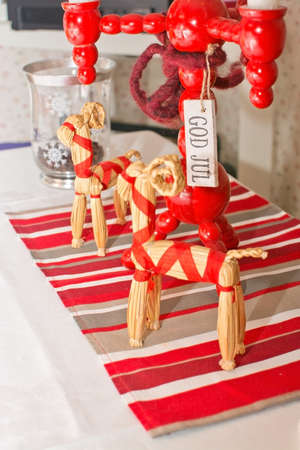 brown goat: Dinner table rustic Christmas setting with straw goats and wooden candle holder in traditional colors red and white, with the words God Jul meaning Merry Christmas, Sweden.