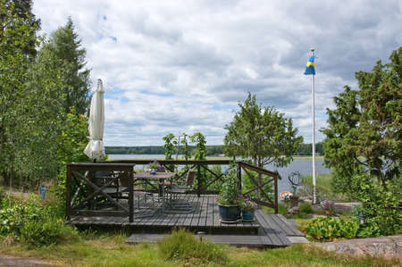 seating area: VARMLAND, SWEDEN - JUNE 20, 2014: Seating area with parasol and Swedish flag near lake on a sunny summer day on June 20, 2014 in Varmland, Sweden.