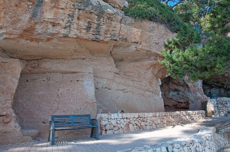 drystone: Bench under massive limestone rock formation with cracks and drystone wall on a sunny summer day in Porto Cristo, Mallorca, Balearic islands, Spain.