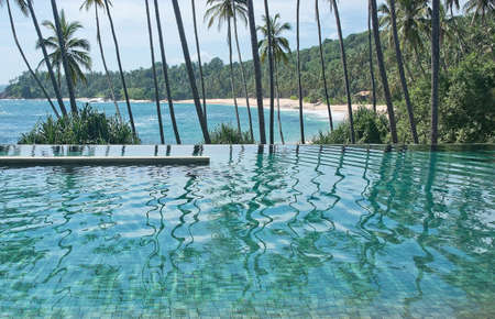 eternity: Eternity swimming pool above sandy paradise beach and palm trees in tropical landscape.