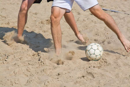 Beach soccer leg closeup and ball with soft sand speed cloud