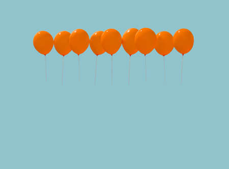 Nine orange balloons soaring against light blue sky with copy space in vintage blue tone.