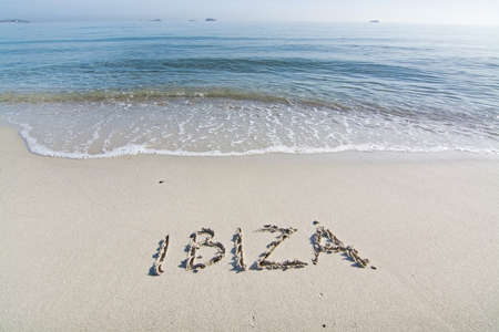 Ibiza written in sand on beach with wave in Ibiza, Balearic islands, Spain