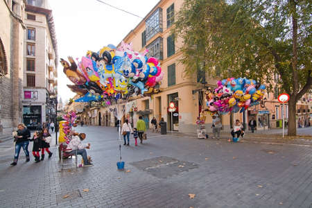 palma: PALMA DE MALLORCA, BALEARIC ISLANDS, SPAIN - DECEMBER 13, 2015: Helium balloon vendors in a Palma street on December 13, 2015 in Palma de Mallorca, Balearic islands, Spain