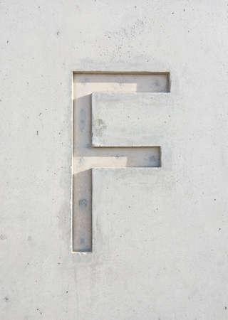 The letter F cut in grayish white stone design element