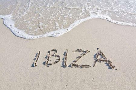 springbreak: Ibiza written in sand on beach with wave in Ibiza, Balearic islands, Spain