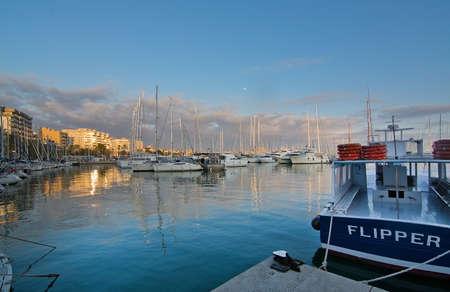 paseo: PALMA, MALLORCA, BALEARIC ISLANDS, SPAIN - DECEMBER 22, 2015: Palma marina boats moored along the Paseo Maritimo and nearly full moon in the blue sky at dusk on December 22, 2015 in Palma de Mallorca, Balearic islands, Spain