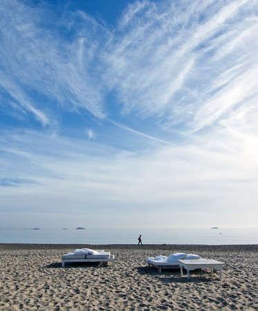 den: PLAYA DEN BOSSA, IBIZA, SPAIN - DECEMBER 17, 2015: White sunbeds on the sandy Playa den Bossa beach on a sunny morning on December 17, 2015 in Playa den Bossa, Ibiza, Spain.