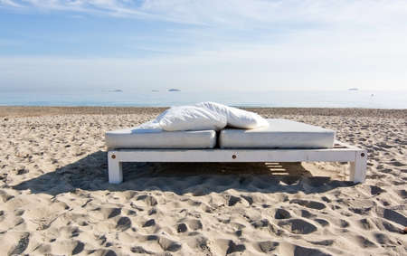 sunbeds: White sunbed on sandy beach with ocean view on a sunny morning in Ibiza, Spain. Stock Photo