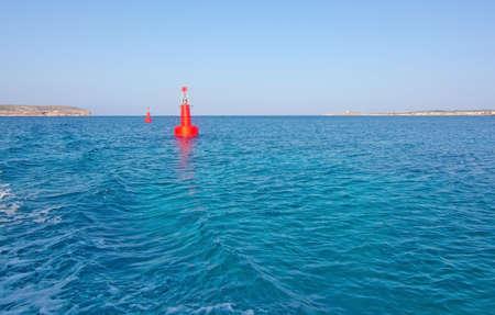 blue lagoon: luce rossa boa in baia dalla gita in barca a laguna blu nell'isola di Comino, Malta.