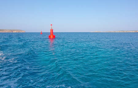 blue lagoon: Red buoy light in bay from boat trip to blue lagoon in Comino island, Malta.