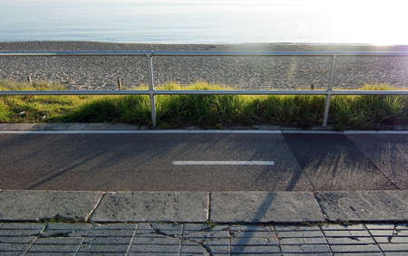 bicycling: Grass and sand along seaside bicycling concrete track with fence and sunshine along the Mediterranean on a sunny day on December 22, 2015 in Palma de Mallorca, Balearic islands, Spain