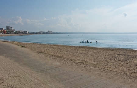 spanish landscapes: CAN PASTILLA, MALLORCA, BALEARIC ISLANDS, SPAIN - DECEMBER 13, 2015: Winter beach with local surfers and stand up paddlers near marina and on sandy Playa de Palma on December 13, 2015 in Balearic islands, Spain