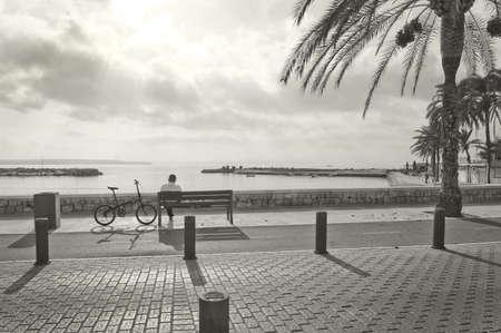stark: CAN PASTILLA, MALLORCA, BALEARIC ISLANDS, SPAIN - DECEMBER 14, 2015: Man rests on a bench in stark sunshine monochrome sepia image on December 14, 2015 in Mallorca, Balearic islands, Spain