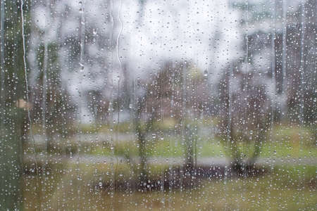 looking out: Window with raindrop pattern looking out on unfocused gray and green landscape with tree abstract background.