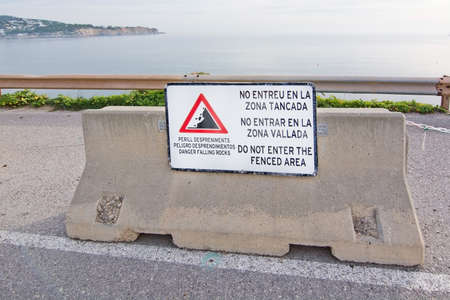 steep cliff sign: IBIZA, BALEARIC ISLANDS, SPAIN - DECEMBER 17, 2015: Warning sign to enter fenced area near fence on steep cliff on December 17, 2015 in Ibiza, Balearic islands, Spain