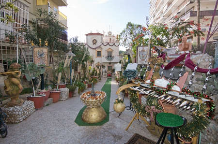amadeus: CALA MAYOR, MAJORCA, SPAIN - DECEMBER 19, 2015: Amadeus Culture decor store inside iron gate with clocks, statues, sculptures, painted items, pots and a windmill on December 19, 2015 in Cala Mayor, Majorca, Balearic islands, Spain