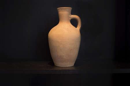 Terracotta vase earthenware household item handmade on a dark shelf isolated on black. Stok Fotoğraf