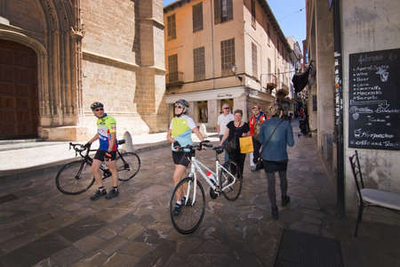 bicyclists: PALMA DE MALLORCA, BALEARIC ISLANDS, SPAIN - APRIL 13, 2016: Bicyclists in Old Town shopping street in Palma de Mallorca, Balearic islands, Spain on April 13, 2016. Editorial