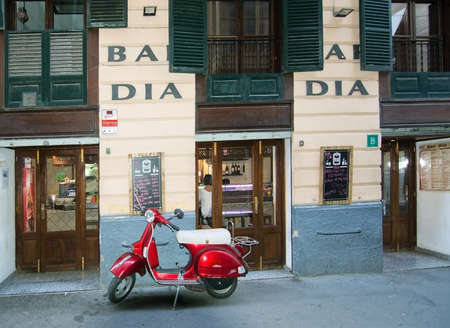 carrer: PALMA DE MALLORCA, BALEARIC ISLANDS, SPAIN - APRIL 7, 2016: Red vespa scooter parked in front of Bar Dia Restaurant on Carrer des Apuntadores in Palma de Mallorca, Balearic islands, Spain on April 7, 2016.