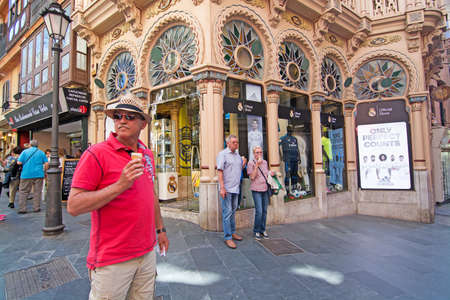real madrid: PALMA DE MALLORCA, BALEARIC ISLANDS, SPAIN - APRIL 13, 2016: Man in red shirt, hat and sunshades enjoys an icecream in front of Real Madrid store in beautiful Can Corbella art nouveau building, housing the Real Madrid sports store, in Palma de Mallorca, B