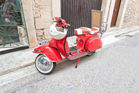 laquered: SANTANYI, MALLORCA, BALEARIC ISLANDS, SPAIN - APRIL 30, 2016: Red beautiful vintage vespa with helmet parked in the street in Santanyi, Mallorca, Balearic islands, Spain on April 30, 2016.