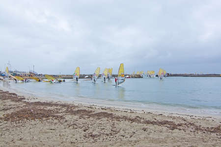 windsurfers: CAN PASTILLA, MALLORCA, SPAIN - APRIL 1, 2016: Windsurfers in yellow sails take off at an International windsurfing competition in rainy weather in Playa de Palma, Mallorca, Balearic islands, Spain on April 1, 2016.